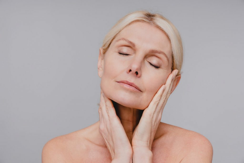 Beautiful aged white woman touching her clean pure face with her eyes closed