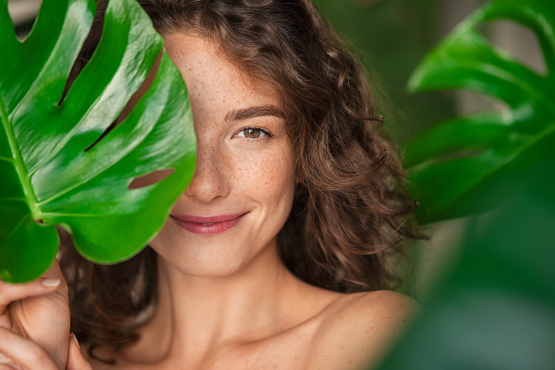 Close up face of beautiful young woman covering her face by green monstera leaf while looking at camera