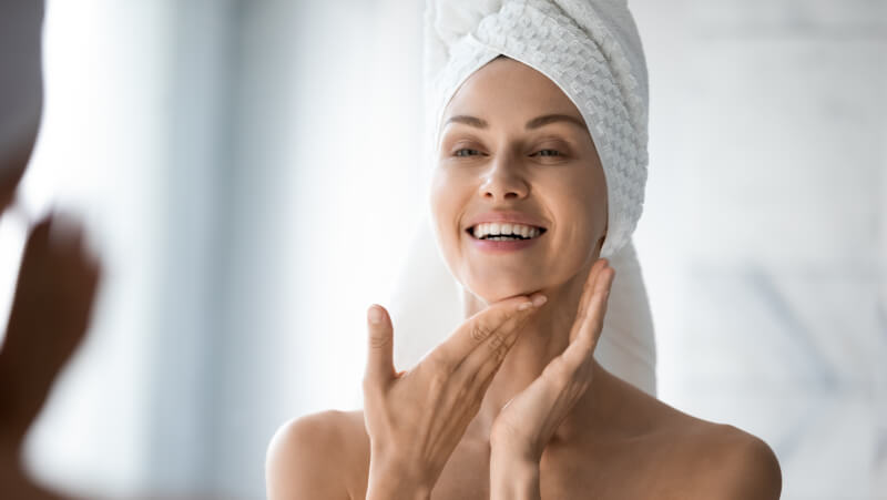 Happy confident young lady with towel on head look in bathroom mirror